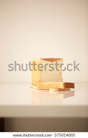 Sliced bread on white table - stock photo