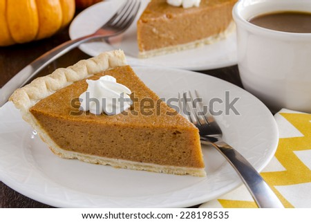 2 slices of fresh pumpkin pie sitting on white plates with cup of coffee, fork and gold chevron napkin - stock photo