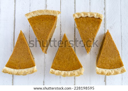 5 slices of homemade pumpkin pie in row sitting on white wooden table - stock photo