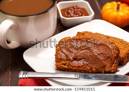 2 slices of pumpkin bread with pumpkin butter spread sitting on white plate with a large cup of fresh brewed coffee - stock photo