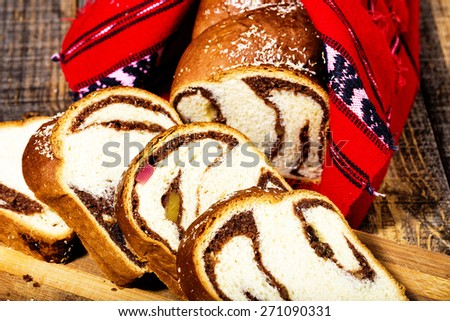 Slices of Romanian sponge cake with red traditional towel with manual stitch on wooden board - stock photo
