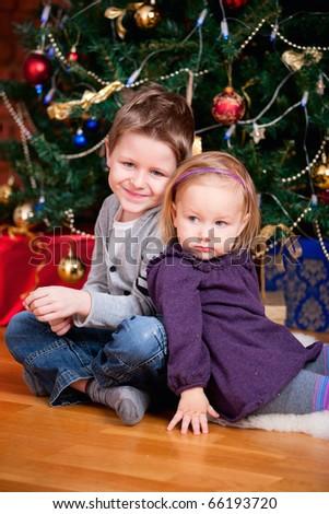2 small kids sitting near beautiful Christmas tree - stock photo