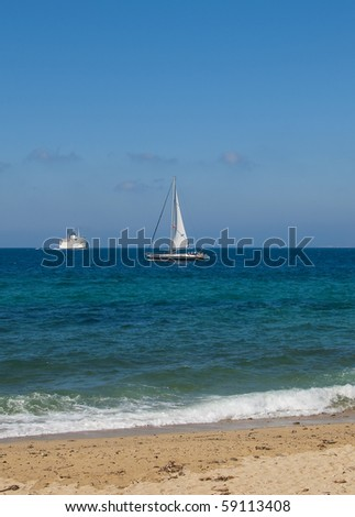 Small yacht in the blue sea off the coast - stock photo