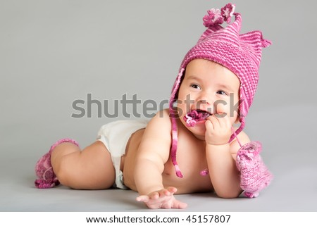 Smiling baby girl in pink cap lie on gray background - stock photo