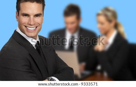Smiling businessman and team. Over blue background - stock photo