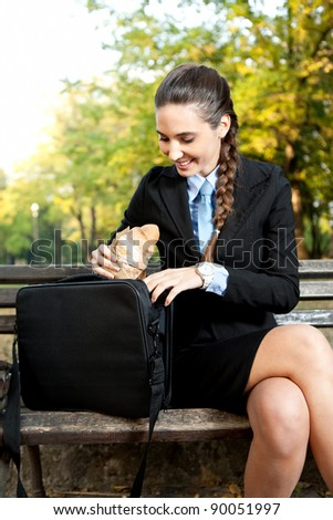 smiling businesswoman sitting  on bench in  park, business  break