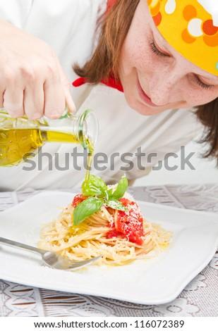 smiling chef garnish an Italian pasta dish - stock photo