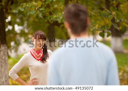 Smiling girl behind blurry boy against autumn landscape.