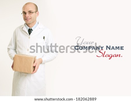Smiling man in  a lab coat carrying a parcel  - stock photo