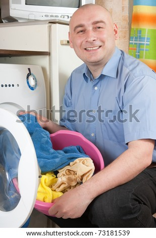 Smiling men loading the washing machine. Cleaning and Laundry - stock photo