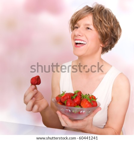 Smiling woman in good mood eating strawberries - stock photo