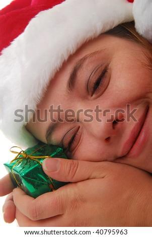 smiling woman wearing Santa hat holding gift - stock photo
