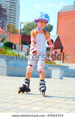 smiling 5 year old girl speedy going on her in-line skates - stock photo