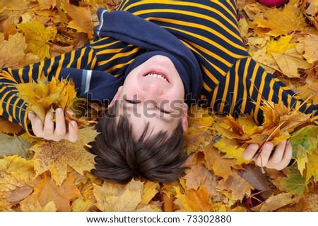 Smiling young boy covered with Autumnal leaves. - stock photo