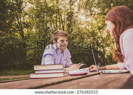 Smiling Young students couple sitting on a bench learning preparing for an exam in a city park.Students using tablet and laptop.Technology.Park.Preparing for Exam - stock photo