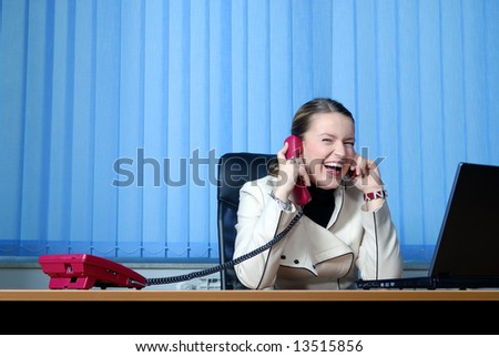 .smilling young businesswoman talking by phone and working on laptop