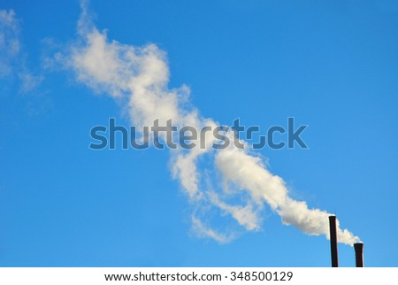Smoke from smokestack of a traditional rice mill. Industrial pollution smoke from chimney on blue sky background with copy space. Global warming  - stock photo