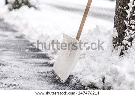 snow shovel standing in the snow - stock photo