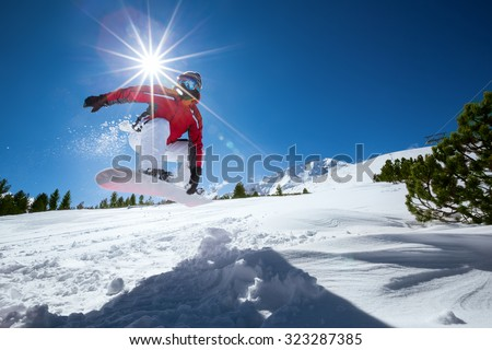 Snowboarder taking a jump in fresh snow. - stock photo