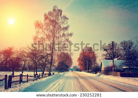 Snowy rural landscape with road at sunset. Ukrainian village, Europe.  - stock photo