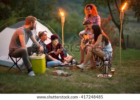 Socializing youngsters in front of tent with beer, guitar and drums at night  - stock photo