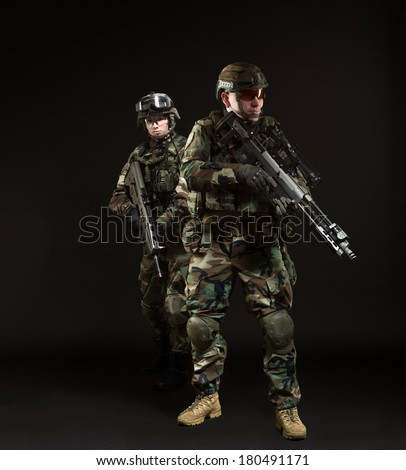 soldiers in full gear. Military man woman over black background.