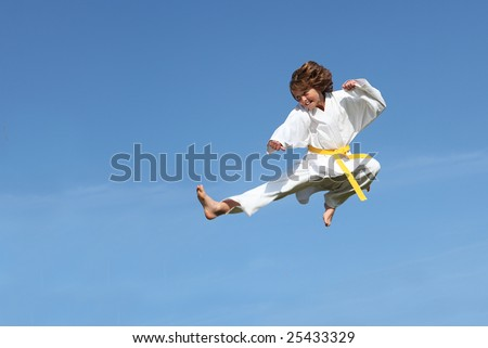 (SOME MOTION BLUR)Karate kid doing karate kick - stock photo
