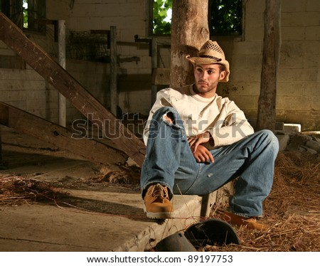 20 Something Ranch Hand resting in old barn - stock photo