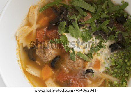soup of beef meatballs, tomatoes, pasta, olives, and  green herbs - stock photo