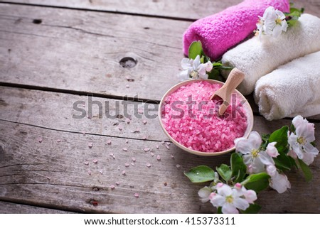 Spa or wellness  organic product. Pink sea salt in bowl, towels  and flowers on aged wooden background. Selective focus. Place for text. - stock photo