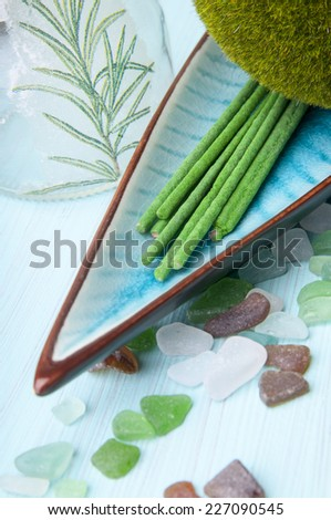 Spa Products Promoting Wellbeing. Green aromatic sticks, stones on the wooden table - stock photo