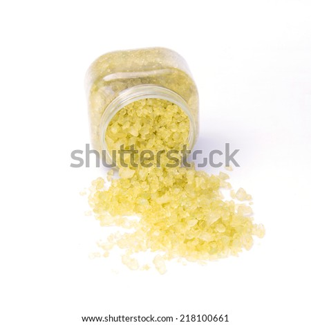 Spa treatment-scented bath salt pour from plastic bottle on white background - stock photo