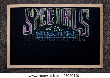 """Specials Of The Month"" Written With Real Chalk On A Black Board - stock photo"