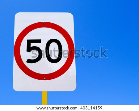 50 speed limit sign on clear blue sky - stock photo
