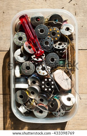 Spools and accessory in plastic box for sewing machine in tailor shop.   - stock photo