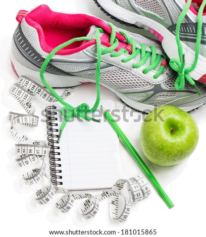 Sports shoes, notebook, pencil and fresh apple isolated on white. Planning of a diet. - stock photo