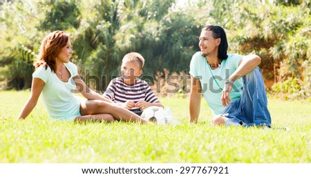 Sporty family of three resting at summer park