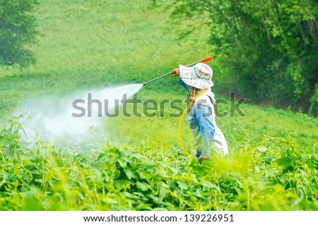 Spraying pesticides on field,  - stock photo