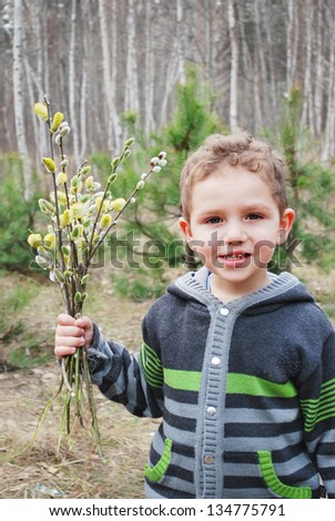 Spring boy stands in a forest and holds a bouquet of pussy willow - stock photo