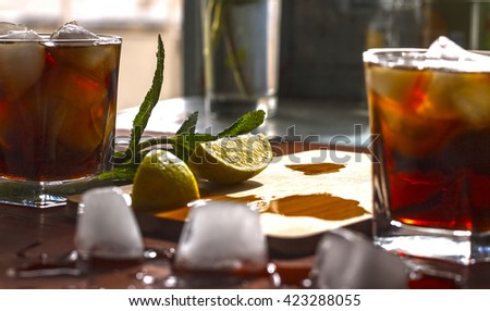 square image. rum cocktail in a glass with ice, lime, mint, bread on a wooden table, brandy