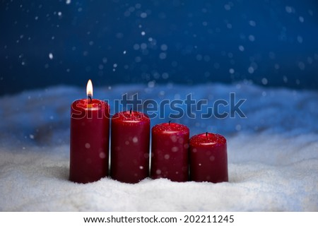 1st Advent candles in snow and snowfall - stock photo