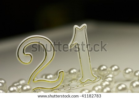 21st birthday sign surrounded by pearls, a celebratory concept - stock photo