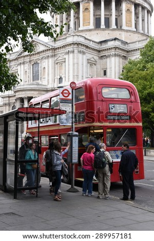 21st June 2015: People Boarding on Iconic Old Style Red Bus at Saint Paul Cathedral Bus Station, St Paul Cathedral historic religious monument, must visit if you are in London - stock photo