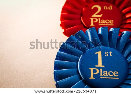 1st place blue winners rosette or badge to be awarded as a prize to the winner of a competition made of pleated blue ribbon with central text in gold with a 2nd place red rosette behind - stock photo