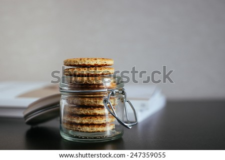 Stack of dutch waffles with caramel in a jar, selective focus
