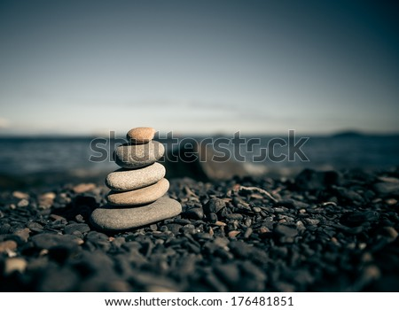 Stack of zen stones on beach. Selective focus and shallow depth of field. Color toned image. - stock photo