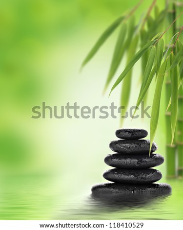 Stacked hot stones or massage stones and bamboo - stock photo