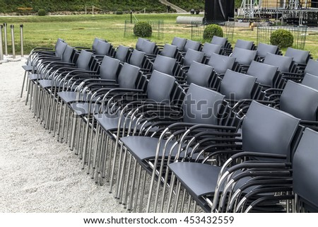 Stacked rows of black chairs