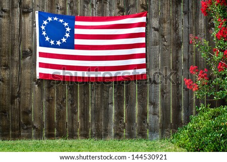13 Star American flag, the Betsy Ross flag, displayed on rustic wooden fence - stock photo