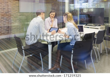 Start-up business team in meeting, working on computer - stock photo